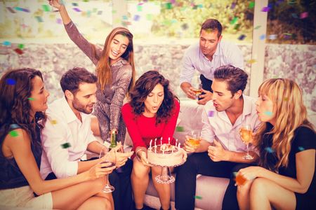 Woman blowing birthday candles with friends against flying colours