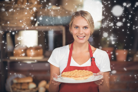 Snow falling against pretty waitress holding a plate of cake Stock Photo