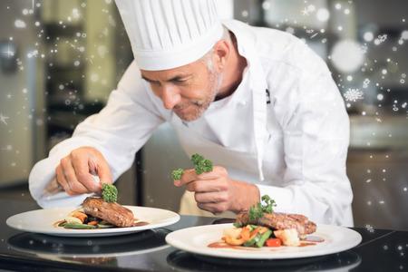 La neige qui tombe contre concentré chef mâle garnissant la nourriture dans la cuisine