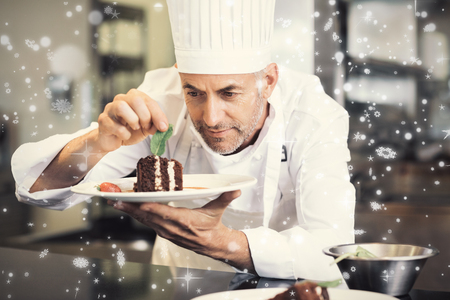 Snow falling against concentrated male pastry chef decorating dessert in kitchen Stock Photo