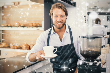 Snow falling against handsome barista offering a cup of coffee to camera