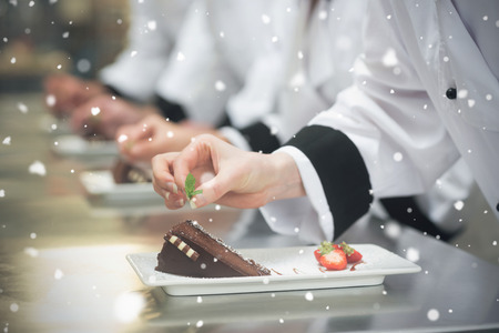 Snow falling against team of chefs in a row garnishing dessert plates