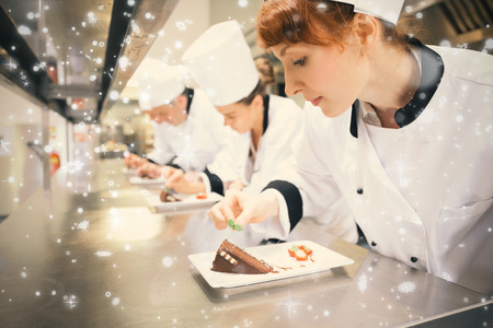 Snow falling against chefs standing in a row garnishing dessert plates