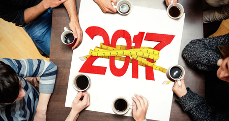 digitally generated image: People sitting around table drinking coffee against digitally generated image of new year with tape measure