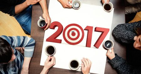 bulls eye: People sitting around table drinking coffee against composite image of numbers with bulls eye arrow Stock Photo
