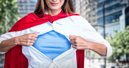 Woman pretending to be superhero against blur view of a modern city
