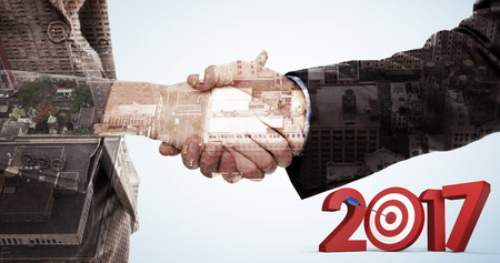 bulls eye: Numbers with bulls eye arrow against composite image of close up of two businesspeople shaking their hands Stock Photo