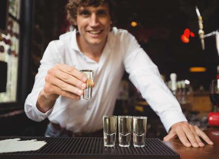 shot glass: Portrait of bartender holding tequila shot glass at bar counter in bar LANG_EVOIMAGES