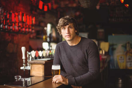 beer pump: Portrait of man with a glass of beer at bar counter in bar LANG_EVOIMAGES