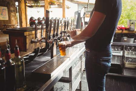 beer pump: Mid section of bar tender filling beer from bar pump at bar counter