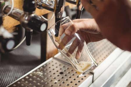 beer pump: Close-up of bar tender filling beer from bar pump at bar counter