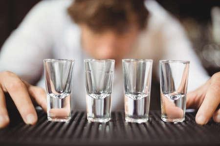 bebidas alcohÓlicas: Bartender preparing and lining shot glasses for alcoholic drinks on bar counter at bar