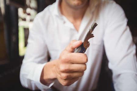 bottle opener: Close-up of bartender a bottle opener at bar counter