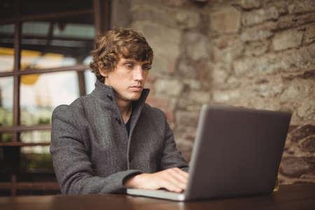 technology: Man using laptop at bar