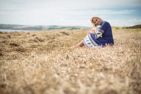 tranquillity: Carefree blonde woman sitting in field LANG_EVOIMAGES