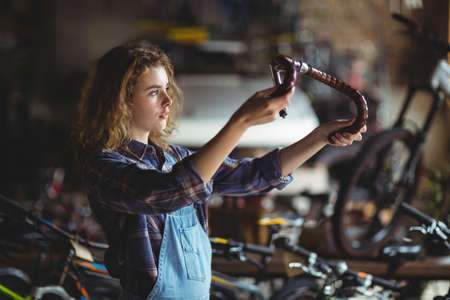 servicewoman: Mechanic examining a bicycle handle bar in workshop LANG_EVOIMAGES