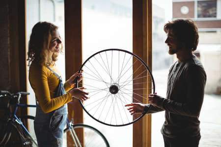servicewoman: Mechanics interacting while examining a bicycle wheel in workshop LANG_EVOIMAGES