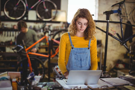 servicewoman: Mechanic using laptop at counter in bicycle shop