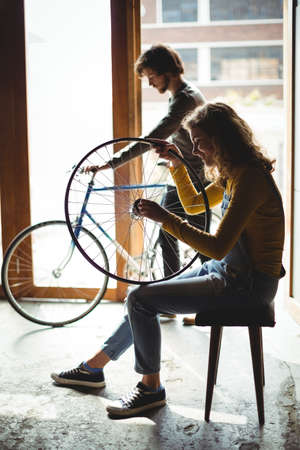 servicewoman: Mechanics examining a bicycle wheel in workshop