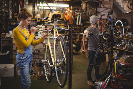 servicewoman: Mechanic repairing a bicycle handle bar in bicycle workshop