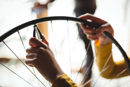 servicewoman: Mechanic examining a bicycle wheel in workshop