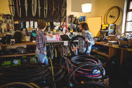 servicewoman: Mechanics selecting tyres in bicycle workshop