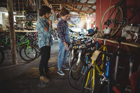 servicewoman: Mechanics examining a bicycle in bicycle workshop