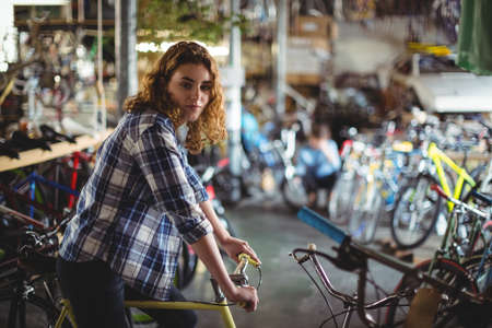 trying: Portrait of beautiful mechanic trying bicycle in workshop
