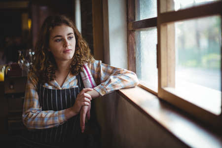 think through: Thoughtful waitress looking through window in workshop