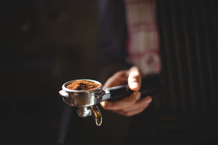 Mid section of waiter holding portafilter filled with ground coffee in café