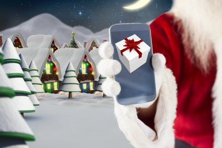 Santa claus hand showing christmas gift on mobile phone screen against digitally generated background Stock Photo