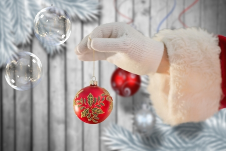 Hand of santa claus holding a christmas bauble against digitally generated
