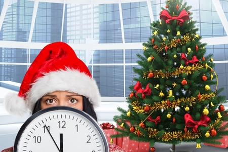 astonishing: Woman in santa hat hiding behind a clock during christmas time