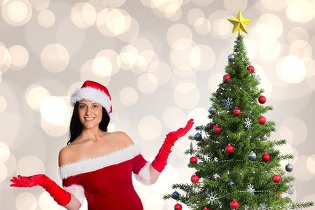 tinsel: Portrait of beautiful woman in santa costumePortrait of beautiful woman in santa costume standing near christmas tree