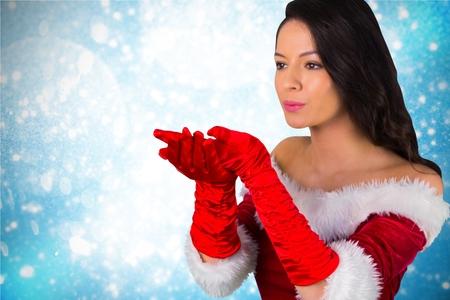 pere noel sexy: Belle femme en costume de père noël soufflant un baiser pendant le temps de Noël