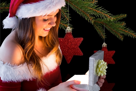 pere noel sexy: Surprised woman in santa costume looking at christmas gift during christmas time