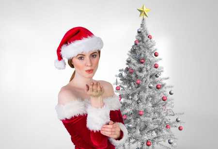flying kiss: Portrait of beautiful woman in santa costume blowing a kiss against white background Stock Photo