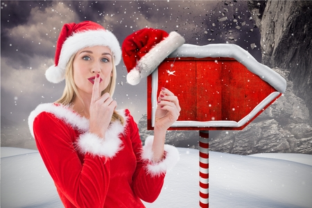 Female santa with finger on lips standing in snowfall during christmas time Stock Photo