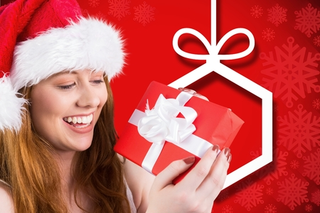 Beautiful woman in santa hat holding a christmas gift against digitally generated background Stock Photo