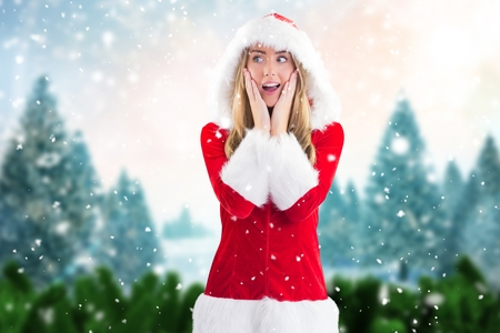Surprised woman in santa costume standing against digitally generated background during christmas time
