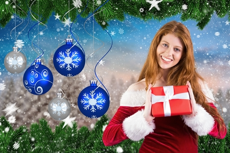 Portrait of beautiful woman in santa hat showing a christmas gifts against digitally generated background Stock Photo