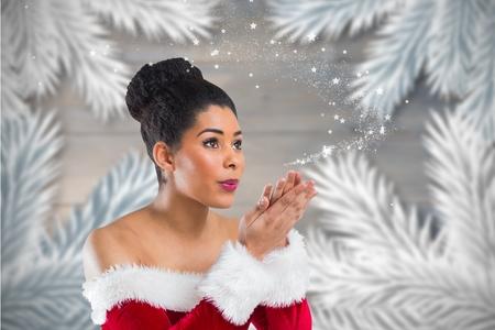 pere noel sexy: Belle femme en père noël flocons costume soufflage de la neige sur le fond généré numériquement pendant le temps de Noël
