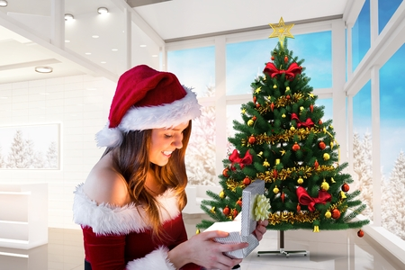 pere noel sexy: Beautiful woman in santa costume looking at christmas gift during christmas time
