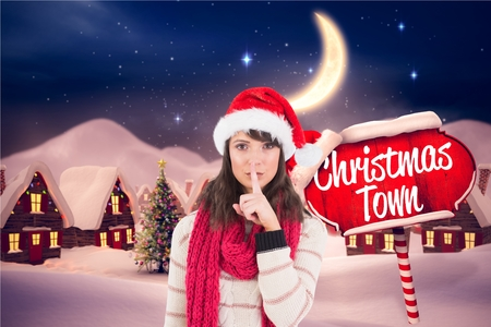 Beautiful woman in santa hat with finger on lips against digitally generated background Stock Photo