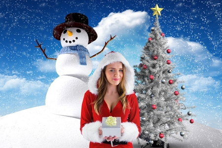 Portrait of beautiful woman in santa costume holding a gift against digitally generated background during christmas time