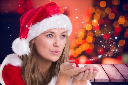 Beautiful woman in santa costume blowing a kiss during christmas time