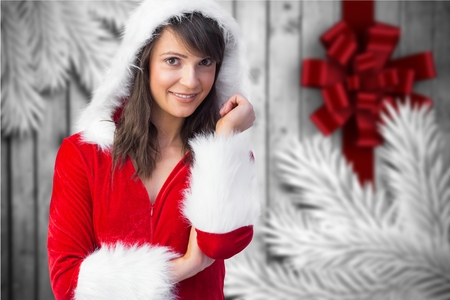 pere noel sexy: Portrait of smiling woman in santa costume standing against digitally generated background