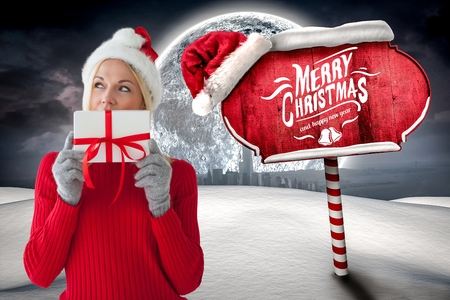 day dreaming: Beautiful woman in santa costume holding christmas gift against digitally generated background Stock Photo