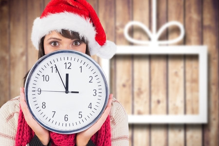 Woman in santa hat covering her face behind clock against digitally generated background