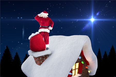 christmas time: Digitally generated image of santa claus standing on house roof during christmas time Stock Photo
